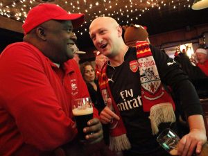 Ron Treausre (left), vocalist at Guns Don't Run talks to Henry (Jamie) Behar (right), guitarist at Guns Don't Run at O'hanlons Bar in Manhattan after a European soccer club, Arsenal game. They have known each other for more than 10 years through Arsenal, which led to Treasure's inculcation into the punk rock band in 2015.