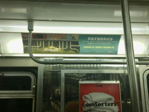 """""""Trash It, Don't Flush It"""" campaign poster in an NYC subway car"""