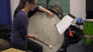 NYU percussion major plays the base drum during the master class in which percussion students prepared for the concert.
